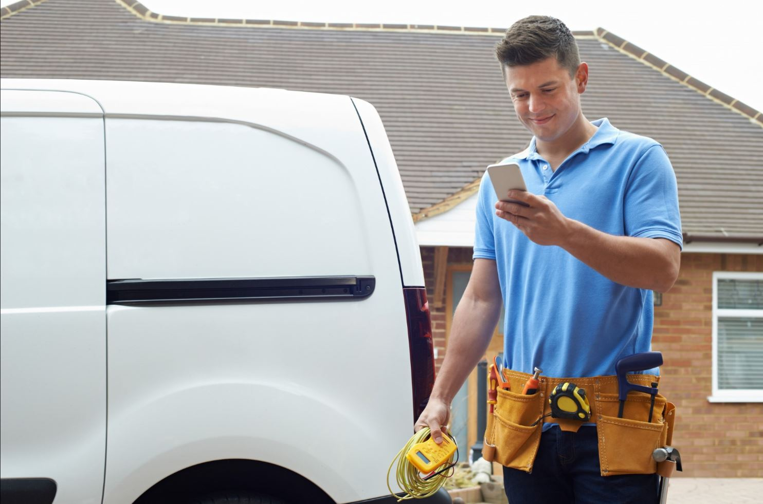 Tradesman looking at his mobile phone smiling.-1